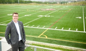 Image of Head of School Jason Rogers in front of the Rundle College football field